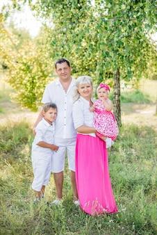 Glücklicher familienspaziergang im sommer in der natur