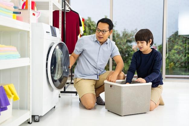 Glücklicher familienvater und kleiner helfer des kindersohns haben spaß und lächeln beim wäschewaschen mit waschmaschine washing