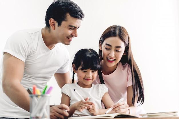 Glücklicher familienvater und mutter mit tochter, die im notizbuch mit bleistift lernen und schreiben, hausaufgaben zu hause machen. bildungskonzept