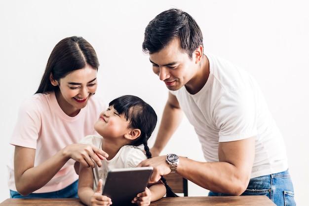 Glücklicher familienvater und -mutter mit tochter, die zusammen im wohnzimmer zu hause sitzt und tablet-computer betrachtet