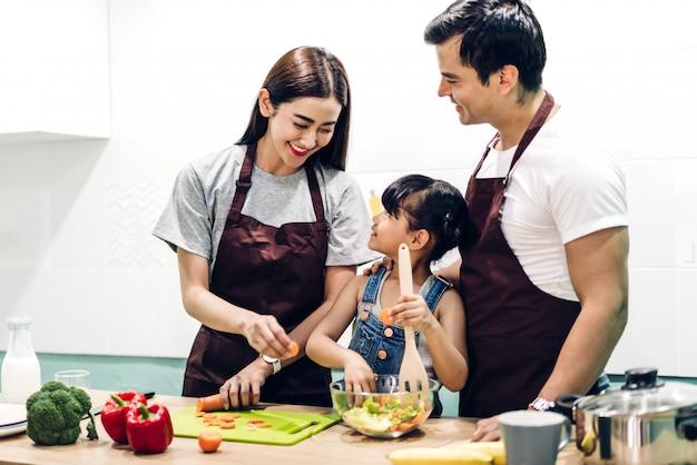 Glücklicher familienvater und mutter mit tochter, die zusammen in der küche kochen und essen zubereiten