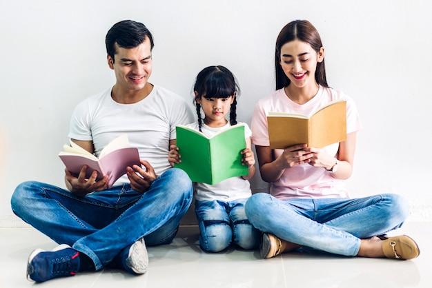 Glücklicher familienvater und mutter mit tochter sitzen und buch zusammenhalten