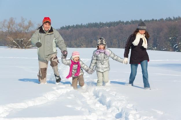 Glücklicher familienwinterspaß draußen. lächelnde eltern mit den kindern, die mit schnee auf winterferien spielen
