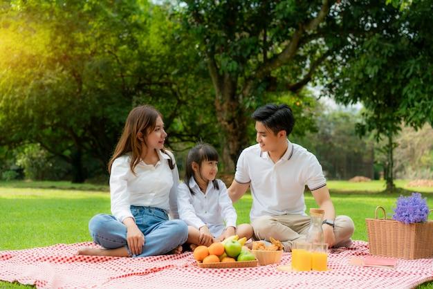 Glücklicher feiertagspicknickmoment der asiatischen jugendlichen familie im park mit mutter und tochter, die vater betrachten und lächeln, um glückliche urlaubszeit zusammen im grünen garten mit obst und essen zu verbringen.