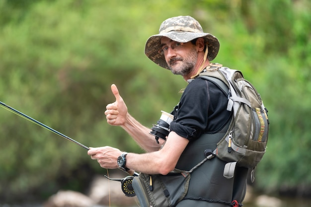 Glücklicher fischer mit einem bart auf der flussbank mit einer angelrute in seinen händen, daumen zeigend. sommerferien.