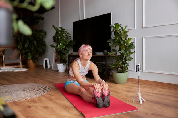 Glücklicher fitnesstrainer nimmt neues video für blog auf und macht vorwärtsbeugen beim sitzen auf der matte