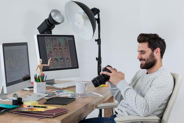 Glücklicher fotograf, der kamera an seinem schreibtisch hält