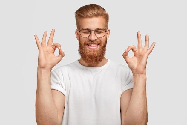 Glücklicher foxy junger mann mit zufriedenem ausdruck, macht okay geste, schließt augen mit glück