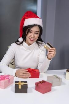 Glücklicher frauenabnutzungs-sankt-hut, der kreditkarte- und weihnachtsgeschenk hält