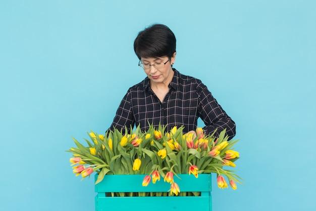 Glücklicher frauenflorist mittleren alters, der brille mit schachtel tulpen auf blauer wand trägt.