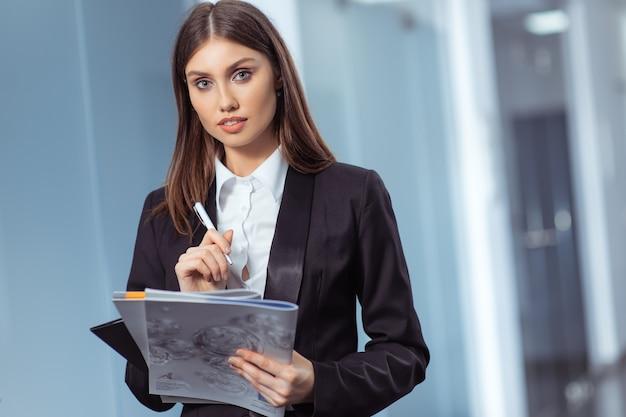 Glücklicher frauenmanager, der im modernen büroinnenraum steht
