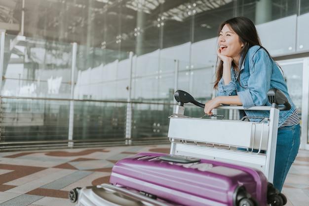 Glücklicher frauenpassagier mit gepäcklaufkatze