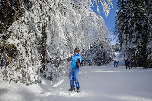 Glücklicher frauenskifahrer auf einer skisteigung im wald