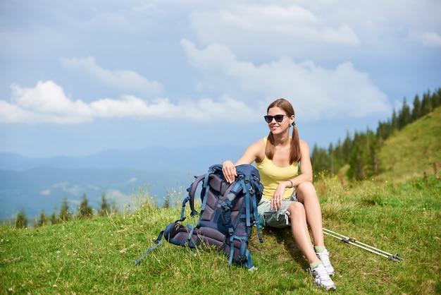 Glücklicher frauentourist, der bergpfad wandert, der auf grasbewachsenem hügel ruht und sommertag in den bergen genießt