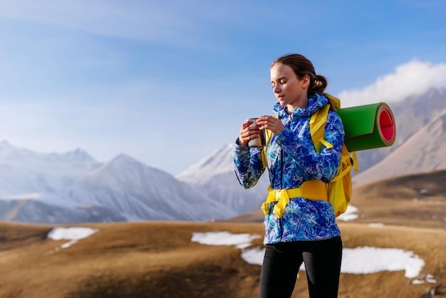 Glücklicher frauentourist trinkt tee auf einem hintergrund der schönen schneebedeckten berge