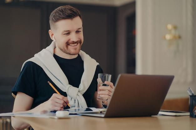 Glücklicher freiberufler oder unternehmer in freizeitkleidung, der am schreibtisch vor einem geöffneten laptop sitzt und im internet surft, ein glas wasser hält und von zu hause aus online arbeitet. freiberufliches konzept