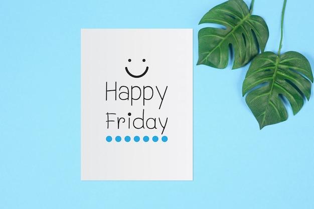 Glücklicher freitag auf weißem blatt mit grünem tropischem palmblatt auf blauem farbhintergrund