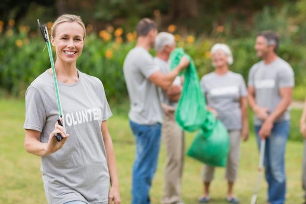 Glücklicher freiwilliger, der abfall sammelt