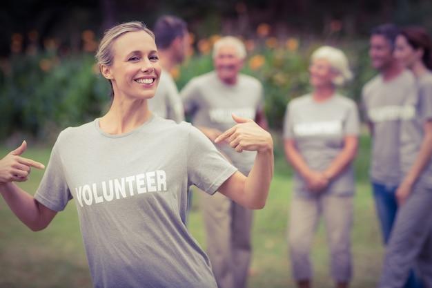 Glücklicher freiwilliger, der ihr t-shirt zur kamera zeigt