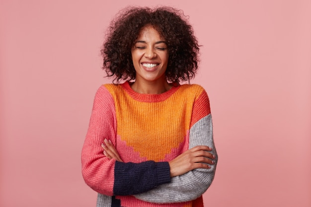 Glücklicher freudiger attraktiver afroamerikaner mit einer afro-frisur schloss die augen und lachte von etwas lustigem, stand mit verschränkten armen, trug bunten pullover, isoliert auf rosa