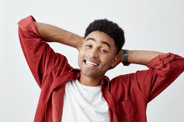 Glücklicher freudiger junger tan-enthäuteter amerikanischer männlicher student mit afro-frisur im weißen t-shirt lächelnd mit den zähnen, händchenhalten hinter dem kopf posierend für universitätsabschlussfoto.