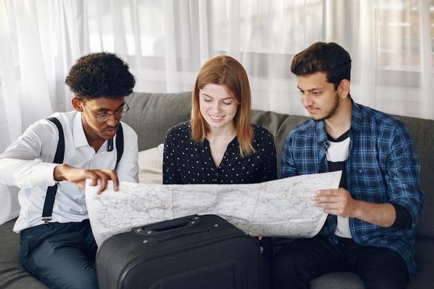 Glücklicher freundeskreis, der eine reise plant. globetrotter inspizieren eine karte zu hause. europäische und indische ethnizität.