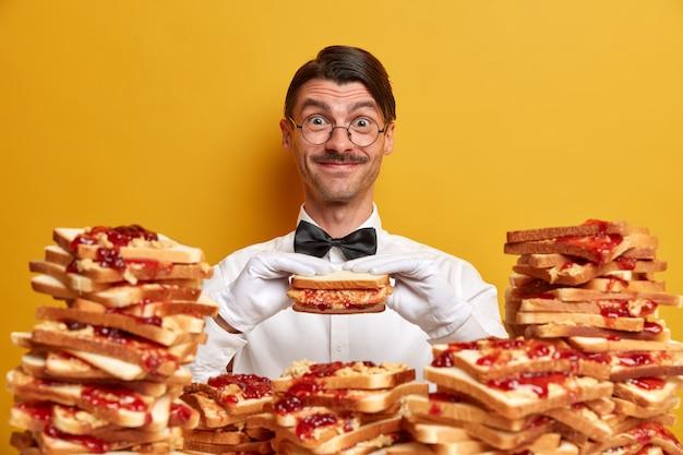 Glücklicher freundlicher kellner hat gelegenheit, leckeres sandwich zu probieren, posiert in der nähe von haufen brot toast, trägt formelles outfit und weiße handschuhe, isoliert auf gelber wand. zeit, burger zu essen