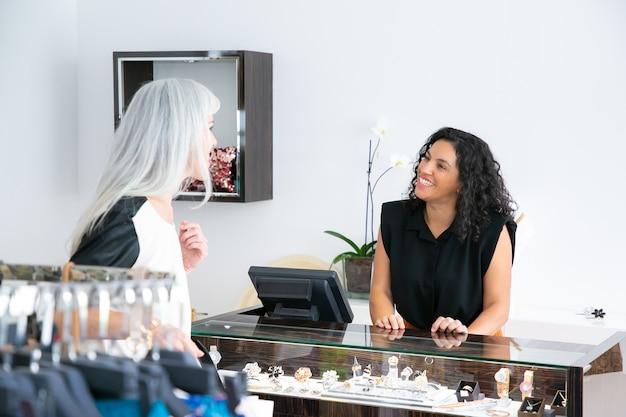 Glücklicher freundlicher verkäufer, der mit kunden im juweliergeschäft spricht. frau berät verkäuferin am schaufenster. einkaufs- und servicekonzept