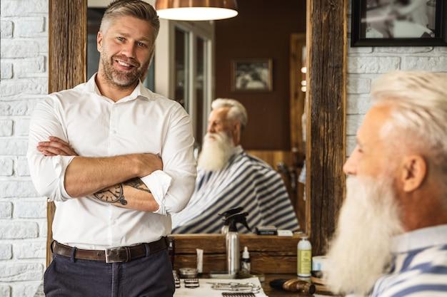 Glücklicher friseur und sein kunde im friseursalon