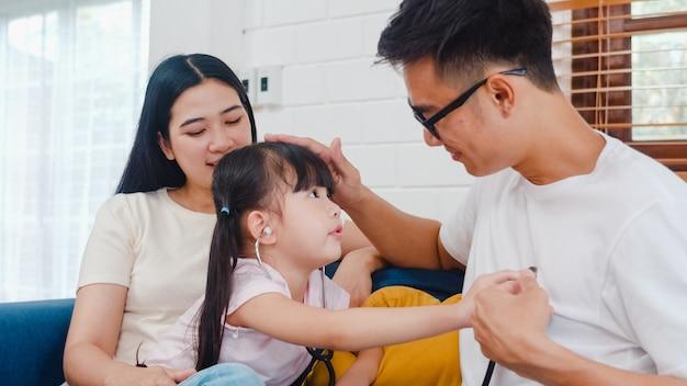 Glücklicher fröhlicher asiatischer familienvater, mutter und tochter, die lustiges spiel als arzt spielen, der spaß auf sofa zu hause hat