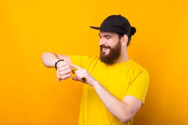 Glücklicher fröhlicher bärtiger hipster-mann, der smartwatch auf gelb verwendet
