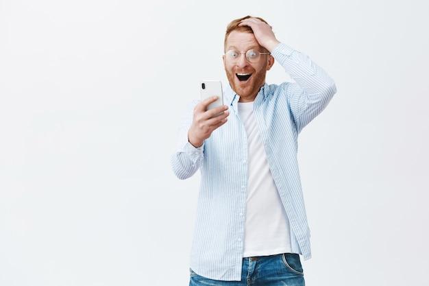 Glücklicher fröhlicher europäer in brille und hemd, haarschnitt berührend, während er erfreut und erstaunt auf den smartphonebildschirm starrt