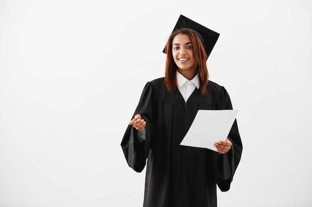 Glücklicher fröhlicher frauenabsolvent lächelnder haltetest über weißer oberfläche