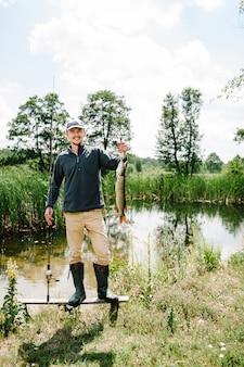 Glücklicher fröhlicher junger fischer halten einen großen fischhecht auf brücke auf hintergrund des sees und der natur.