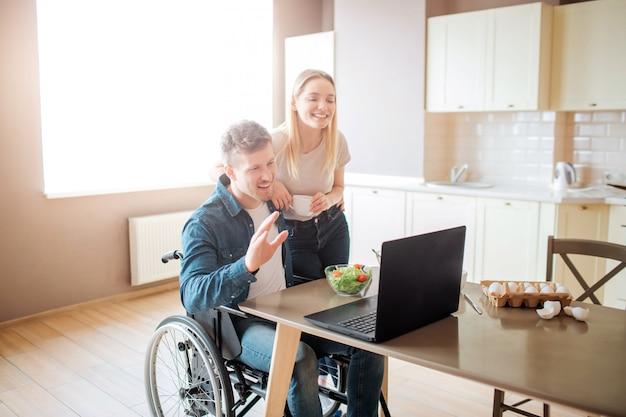 Glücklicher fröhlicher junger mann sitzen am tisch und schauen auf laptop. mann mit behinderung und inklusivität. junge frau steht daneben. film auf lpatop schauen.