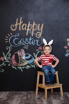 Glücklicher fröhlicher kleiner junge, der hasenohren trägt und ostern feiert