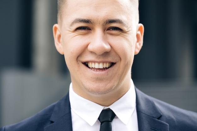 Glücklicher fröhlicher mann, der gerade mit lächeln sieht erfolgreiche karriere attraktiver manager gut aussehend zuversichtlich