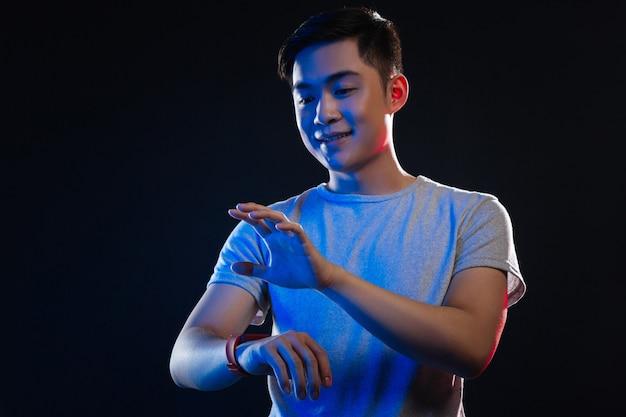Glücklicher fröhlicher mann, der sein handgelenk betrachtet, während er eine smartwatch hat