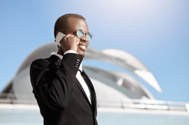 Glücklicher fröhlicher schwarzer geschäftsmann in der formellen kleidung und in der sonnenbrille, die auf smartphone außerhalb des büros sprechen, das früh am morgen aufbaut und termin für geschäftstreffen mit potenziellen partnern macht