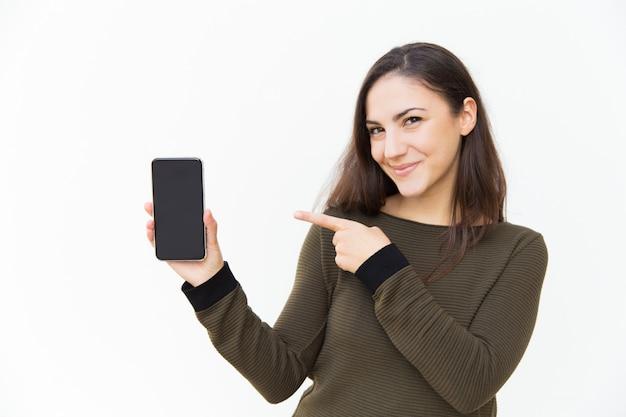 Glücklicher froher mobiltelefonbenutzer, der auf leeren bildschirm zeigt