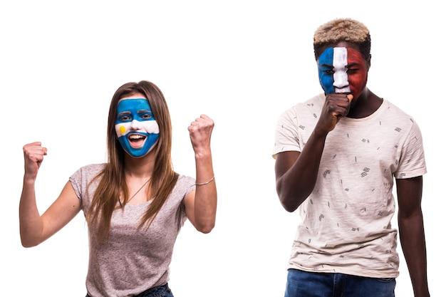 Glücklicher fußballfan von argentinien feiern sieg über verärgerten fußballfan von frankreich mit gemaltem gesicht
