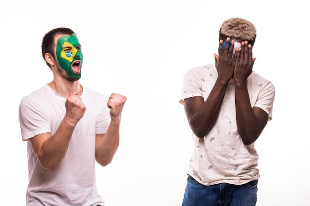 Glücklicher fußballfan von brasilien feiern sieg über verärgerten fußballfan der französischen nationalmannschaften mit gemaltem gesicht lokalisiert auf weißem hintergrund