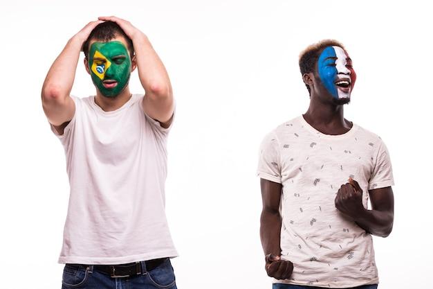 Glücklicher fußballfan von frankreich feiern sieg über verärgerten fußballfan der brasilianischen nationalmannschaften mit gemaltem gesicht lokalisiert auf weißem hintergrund