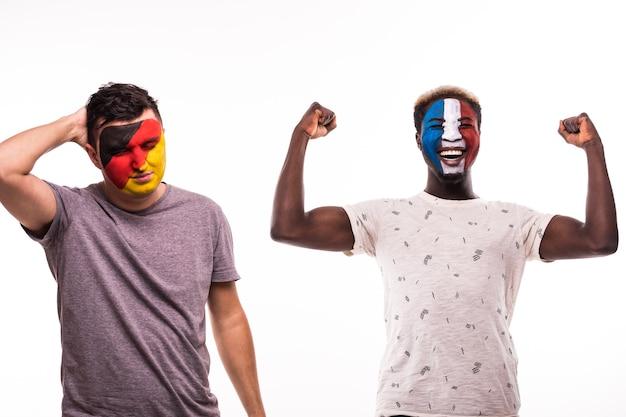Glücklicher fußballfan von frankreich feiern sieg über verärgerten fußballfan der deutschen nationalmannschaften mit gemaltem gesicht lokalisiert auf weißem hintergrund