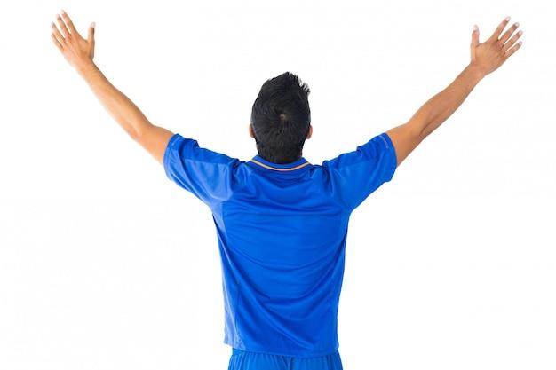 Glücklicher fußballspieler beim blauen feiern
