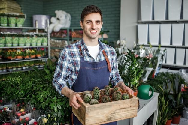 Glücklicher gärtner, der topf mit kaktus in einem blumenladen hält