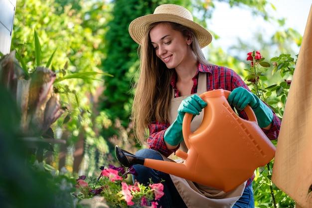 Glücklicher gärtner in hut und schürze mit gießkanne zum gießen von blumen im hausgarten. gartenarbeit und blumenzucht