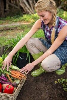 Glücklicher gärtner mit frischem gemüse im garten