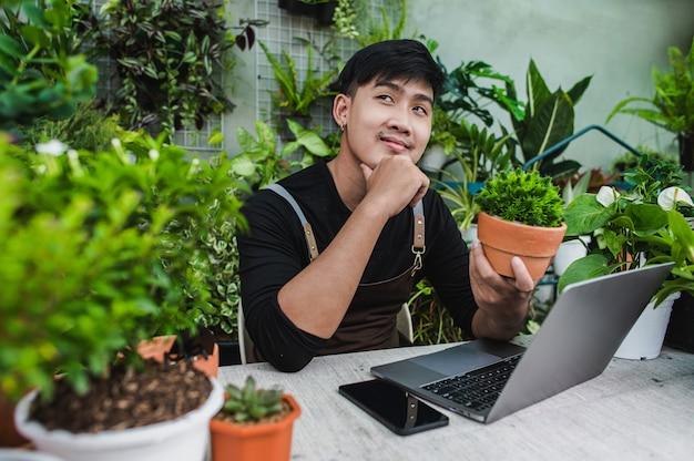 Glücklicher gärtnermann benutzt smartphone und laptop während des online-tutorials zu topfplänen im laden