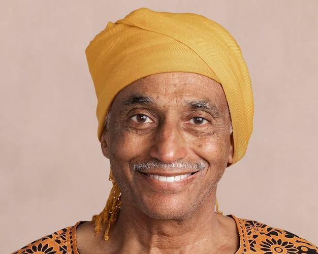 Glücklicher gemischter indischer älterer mann, der ein gelbes turbanmodell trägt